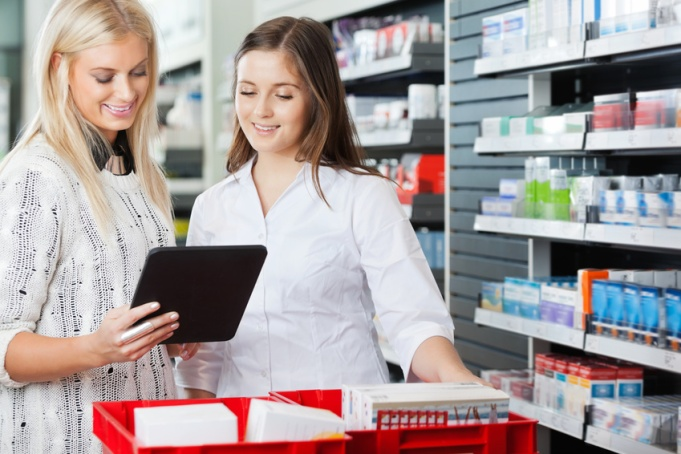 Young pharmacist helping customer in pharmacy with digital tablet